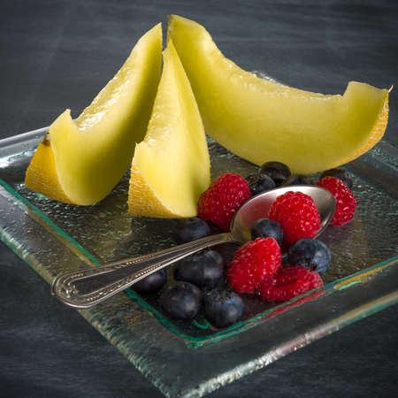 dessert plate: Sano fresco frutta su un piatto da dessert di vetro su sfondo nero concetto di mangiare sano