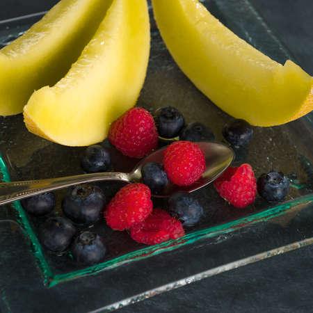 dessert plate: Sano fresco frutta su un piatto da dessert di vetro su sfondo nero Sano concetto di mangiare
