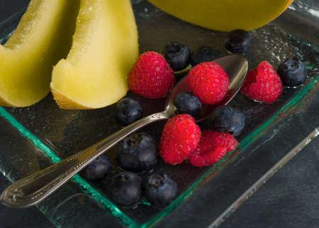 dessert plate: Sano fresco frutta su un piatto da dessert di vetro su sfondo nero concetto di mangia sano