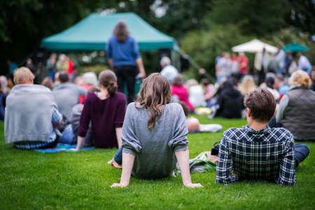 annual event: Amigos sentados en el c�sped, disfrutando de un aire libre de la m�sica, la cultura, el evento de la comunidad, festival