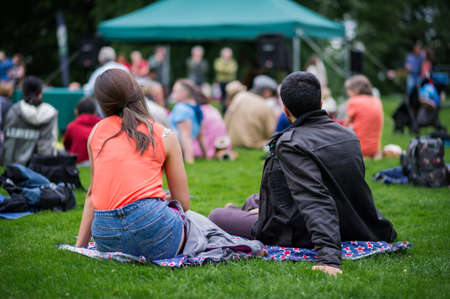 Friends sitting on the grass, enjoying an outdoors music, culture, community event, festival