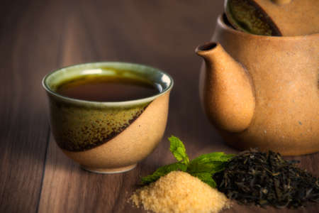 Ceramic teapot, cup of black tea with mint leaves and brown sugar on wooden table