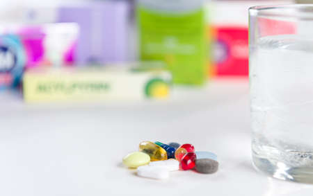 Colorful pills and glass of water, on white background photo