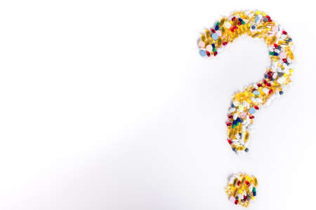 Pills as question mark on white background  Medical concept with copy space photo