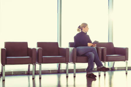 Young woman using her digital tablet pc at an airport lounge, modern waiting room, with backlight  photo