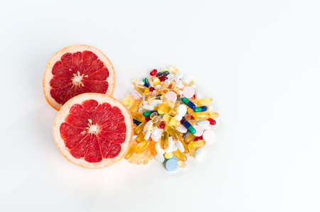 Pink grapefruit and pills, vitamin supplements on white background with copy space, healthy diet concept photo