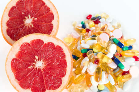 Pink grapefruit and pills, vitamin supplements on white background, healthy diet concept