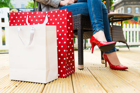 Attractive young female in sexy red high heels enjoying a break after succesfull shopping, detail shot, with copy space