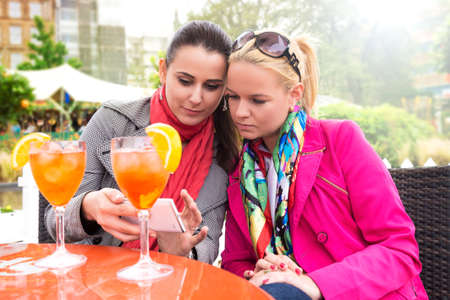 Attractive young women enjoying cocktails in an outdoor bar, while looking at smartphone photo