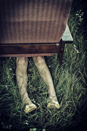 fainted: Dirty female legs stickig out from under an armchair in a field, dark mood unusual concept Stock Photo