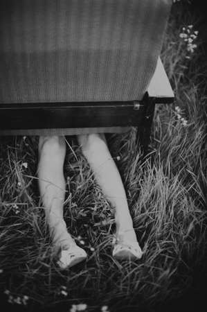 fainted: Dirty female legs sticking out from under an armchair in a field, dark mood unusual concept Stock Photo