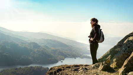 Female hiker on top of the mountain enjoying valley view, Ben A Banco de Imagens