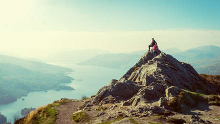 Two female hikers on top of the mountain enjoying valley view, Ben A photo