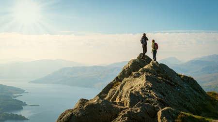 mountain: Two female hikers on top of the mountain enjoying valley view, Ben A
