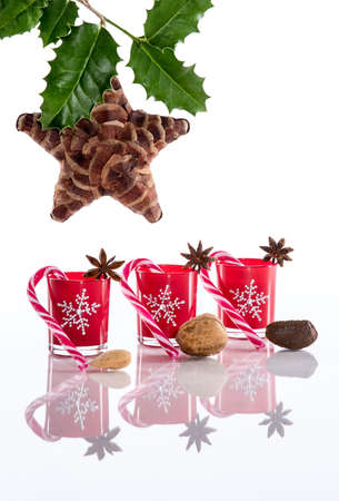 Red candle holders with crystal snowflakes, sugar canes, anise stars, nuts, holy and pine cone star photo