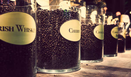 Glass jars with different flavour coffee on display photo