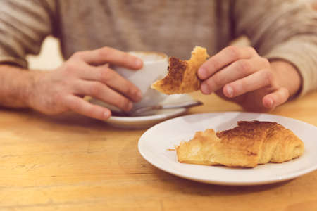 unrecognisable: Detail image of unrecognisable man having breakfast, eating fresh pastry, with copy space Stock Photo