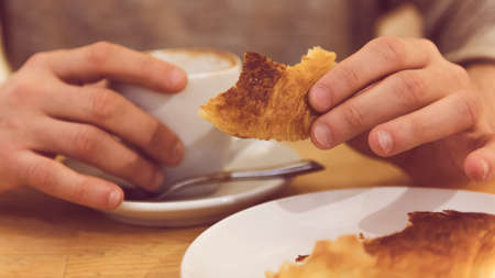 unrecognisable: Detail image of unrecognisable man having breakfast, eating fresh pastry.
