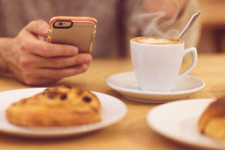 unrecognisable: Always in touch. Detail image of unrecognisable man drinking coffee and holding smart phone while having breakfast in restaurant. Stock Photo