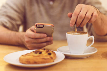 Always in touch. Detail image of unrecognisable man drinking coffee and holding smart phone while having breakfast in restaurant. photo
