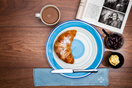 Continental breakfast with coffee, fresh croissants and good magazine photo
