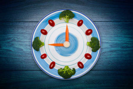Food clock with vegetables, Healthy food concept, on wooden table with copy space photo