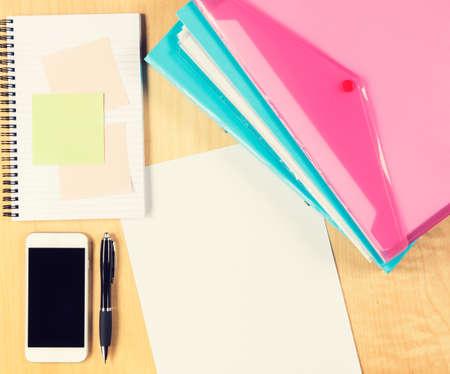 messy office: Tavolo ufficio disordinato con lo smartphone, blocco note e cartelle di riempimento. Vista dall'alto con copia spazio Archivio Fotografico