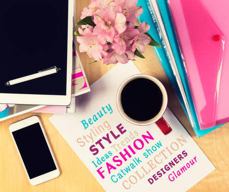 Office table with fashion magazines, digital tablet, smartphone and cup of coffee. View from above with copy space