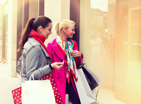 Two attractive young female friends enjoying a day out shopping photo