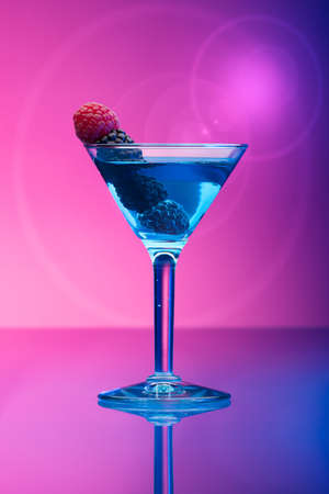 garnished: Colourful cocktail garnished with berries, background with light effects Stock Photo