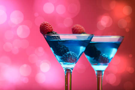 garnished: Colourful cocktails garnished with berries, background with light effects Stock Photo