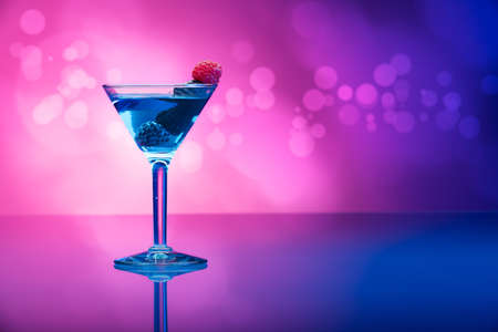 Colourful cocktail garnished with berries, background with light effects Stock Photo