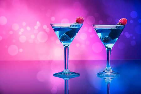 effets lumiere: Des cocktails color�s garnis de baies, de fond avec des effets de lumi�re Banque d'images