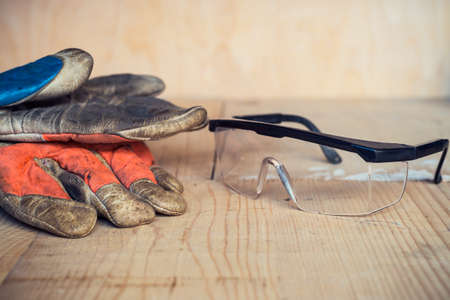 Old used safety glasses and gloves on wooden background