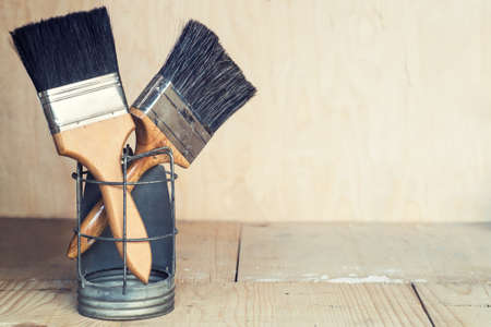 Paint brushes on wooden background, with copy space photo