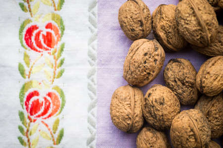 Pile of organic walnuts on vintage kitchen cloth, clean eating concept Stock Photo