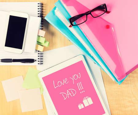 jornada de trabajo: Mesa de oficina sucio con la tarjeta de D�a del padre en la tableta digital. Vista desde arriba, con copia espacio