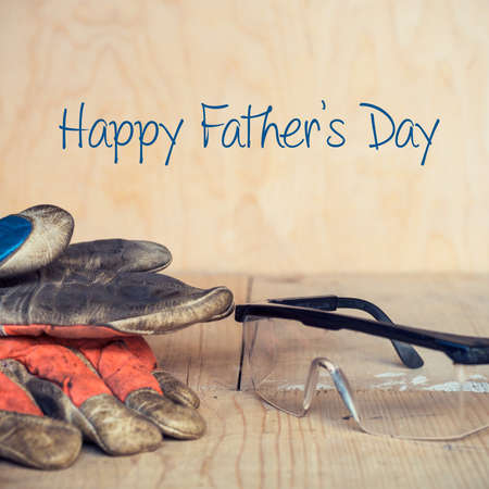 dangerous love: Fathers day concept, Old used safety glasses and gloves on wooden background