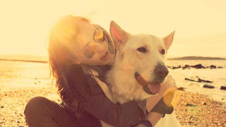 mejores amigas: Chica inconformista juega con el perro en una playa durante la puesta de sol, el efecto de reflejo en la lente fuerte Foto de archivo