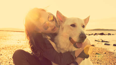 best friends: Hipster girl playing with dog at a beach during sunset, strong lens flare effect