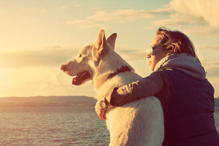 friends hugging: Young attractive girl with her pet dog at a beach, colorised image Stock Photo