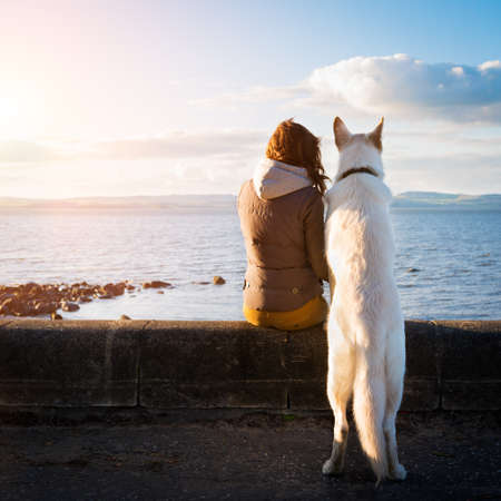 gente feliz: Chica inconformista joven con su perro mascota en una playa, imagen colorised