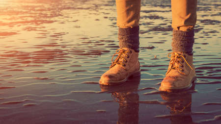 Young girl walking on a beach at low tide, feet detail, adventure concept 스톡 콘텐츠