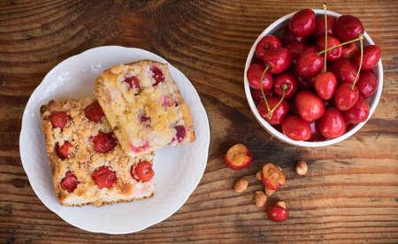 cake pick: Ripe organic homegrown cherries and cherry cake, on wooden background Stock Photo