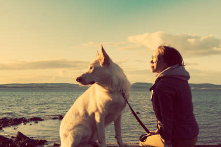 best friends: Young attractive girl with her pet dog at a beach, colorised image Stock Photo
