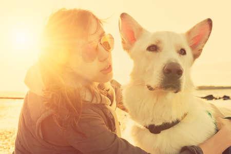 Hipster Mädchen, das mit Hund an einem Strand bei Sonnenuntergang, starke Lens Flare-Effekt Standard-Bild - 41587561