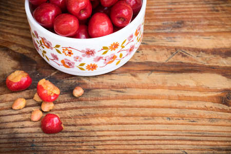 homegrown: Ripe organic homegrown cherries and stones in a vintage ceramic bowl, on wooden background