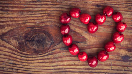 homegrown: Ripe organic homegrown cherries on wooden background in heart shape