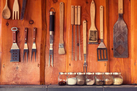 utensil: Grill, bbq area with tools hanging on the wall
