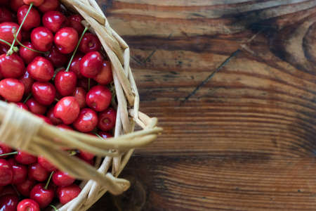 homegrown: Ripe organic homegrown cherries in a basket, on wooden background